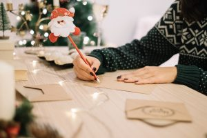 woman writing christmas cards on table in front of christmas tree