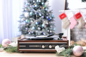 record player in front of christmas tree and fireplace playing classic christmas music