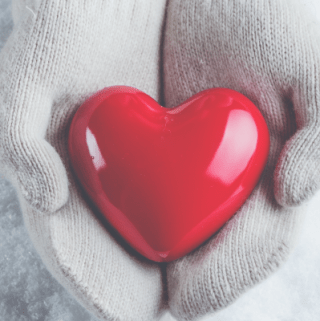 Female hands in white knitted mittens with a glossy red heart on a snow winter background.