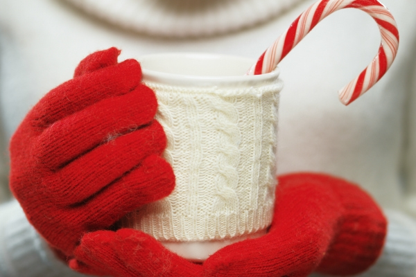 Woman holding winter cup close up on light background.