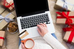 Christmas online shopping top view. Female makes order on laptop with credit card, copy space on screen. Woman sitting among gift boxes and packages. Winter holidays sales