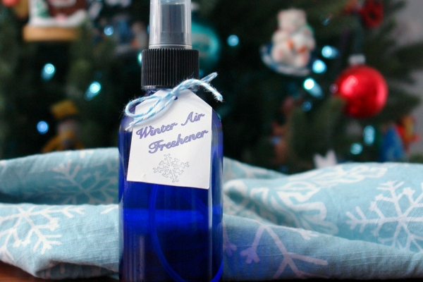Fresh winter air freshener in blue spray bottle with tag sitting on table