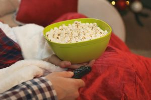 Couple on sofa with tree in background with popcorn while watching tv
