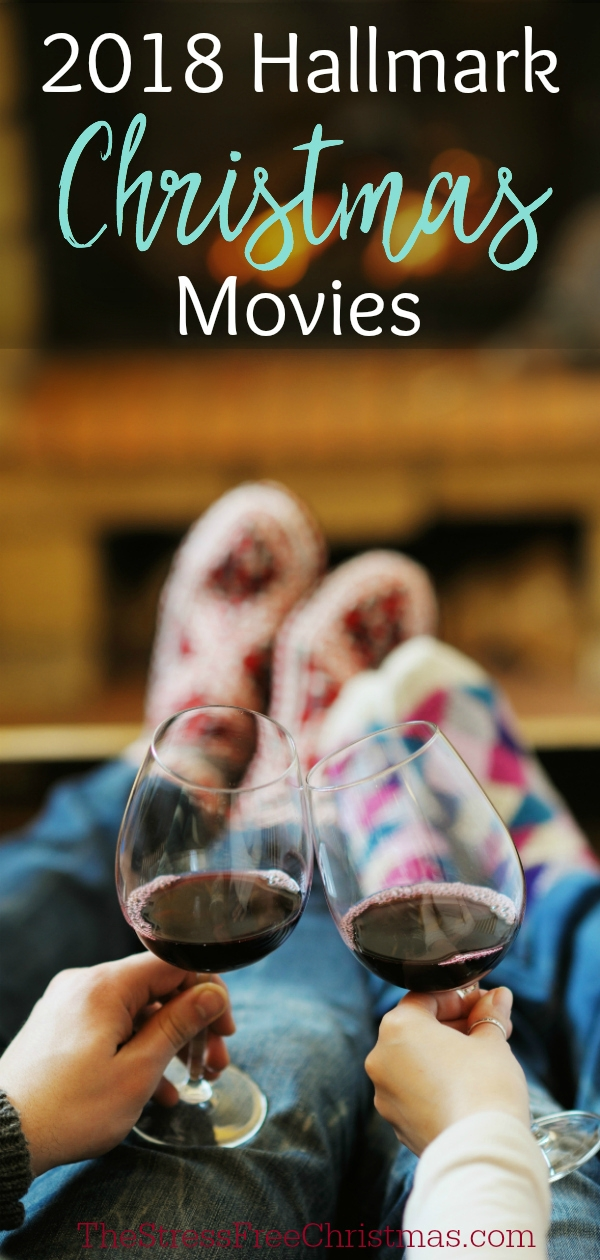 couple in Christmas socks drinking wine in front of fire place watching Hallmark Christmas movies