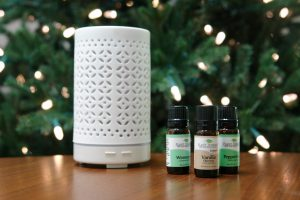 white diffuser and essential oil bottles sitting on table in front of Christmas tree
