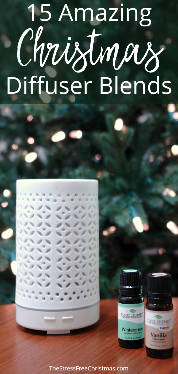 white essential oil diffuser on table with essential oils in front of Christmas tree