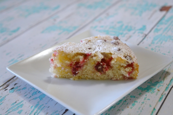 cranberry cake on a white plate on an aqua and white wooden table