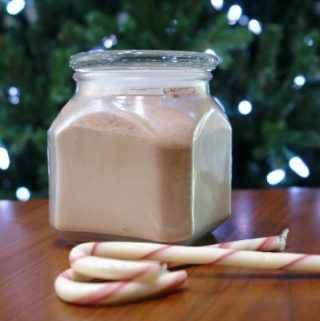jar of homemade hot chocolate mix in front of Christmas tree with candy canes