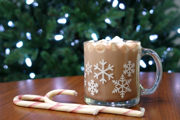 hot chocolate with marshmallows and candy canes in front of Christmas tree