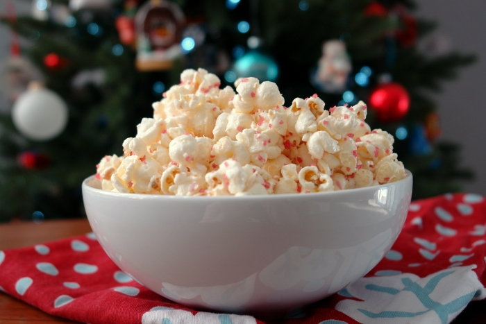 white bowl full of popcorn in front of christmas tree on red christmas towel