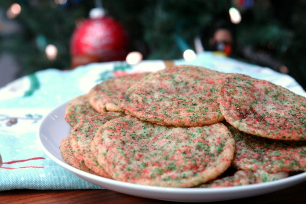 Christmas funfetti cookies on white plate in front of Christmas tree