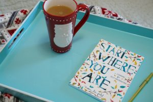 Aqua tray with a journal and Christmas mug on bed with Christmas blanket.
