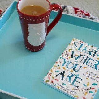 Aqua tray with a journal and Christmas mug on bed with Christmas blanket.