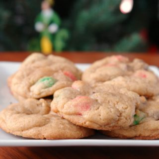christmas M&M cookies on a white plate in front of a Christmas tree