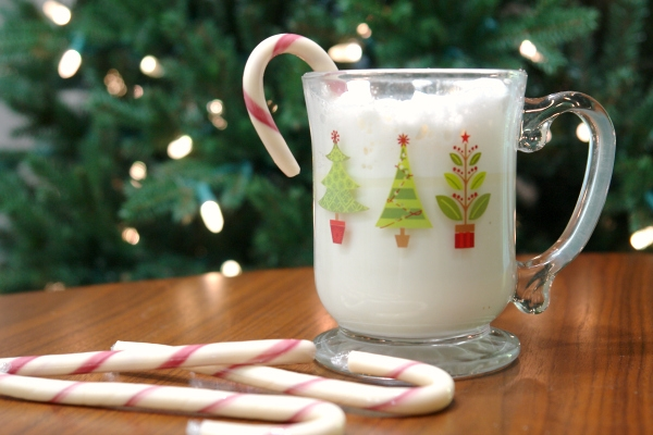 peppermint white hot chocolate in christmas mug with candy cane in front of christmas tree.