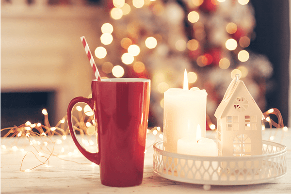 red mug on table in front of Christmas tree with white candle