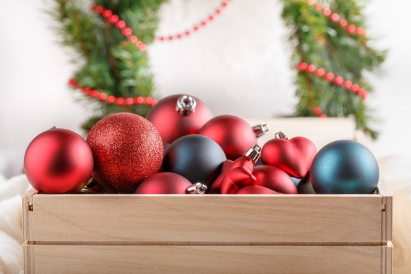Christmas tree ornaments in wooden box on white background.