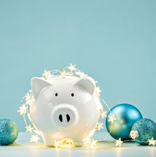 White Piggy bank wrapped in a string of Christmas lights over a blue background.