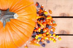 Pumpkin and halloween candy on a wooden crate in background