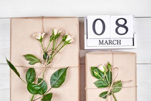 Top view of gift boxes with branch of fresh roses and wooden cube calendar March 8 on white table