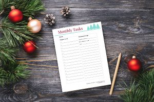monthly tasks printable and Christmas decorations on wooden table