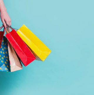 Girl in red dress with shopping bags on blue background
