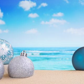 Christmas baubles in the sand on a beach on a bright and sunny day.
