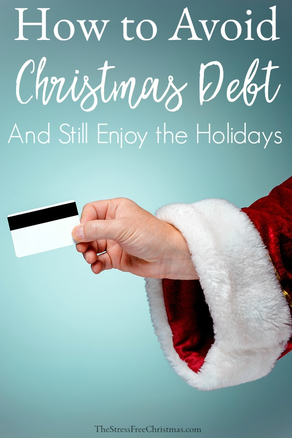 Santa Claus hand holding a credit card on blue studio background