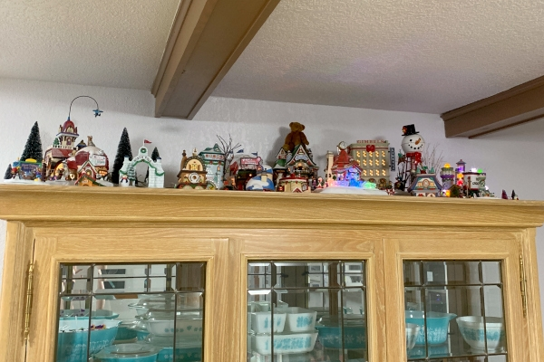 Department 56 Christmas Village on top of china cabinet