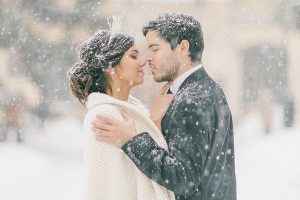 Wedding couple kissing under the snow