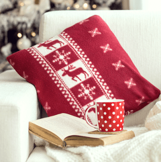 Opened book and a cup of tee on the cozy armchair with warm blanket and cushion on it near Christmas tree.