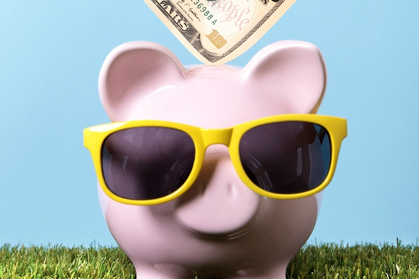 Hand putting a ten dollar bill into a pink piggy bank with sunglasses grass