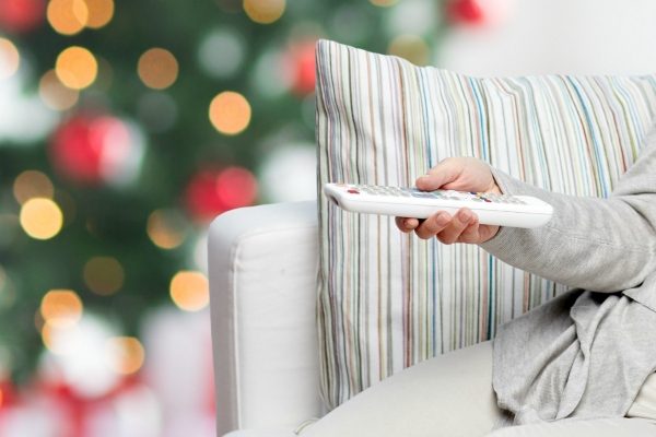 Person on sofa with remote with Christmas tree in background