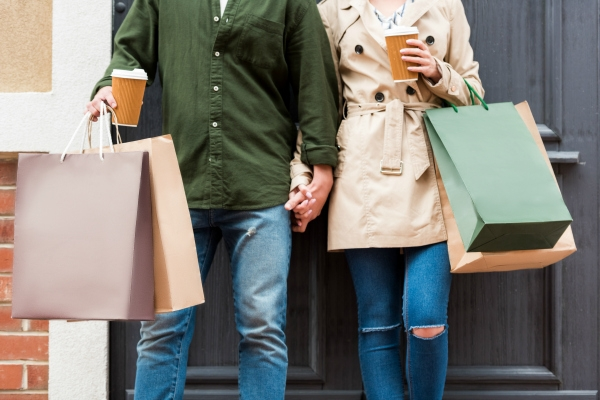 man and woman holding hands, shopping bags and coffee