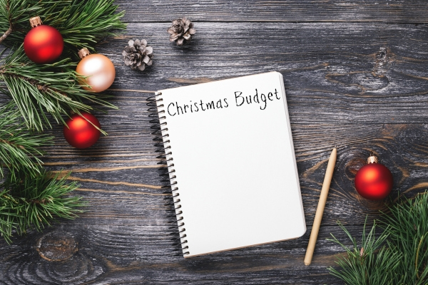 budget notebook and Christmas decorations on wooden table