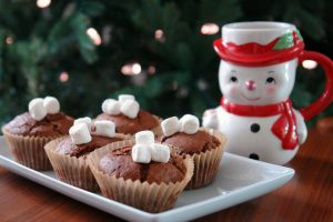 hot chocolate muffins and a snowman mug in front of Christmas tree