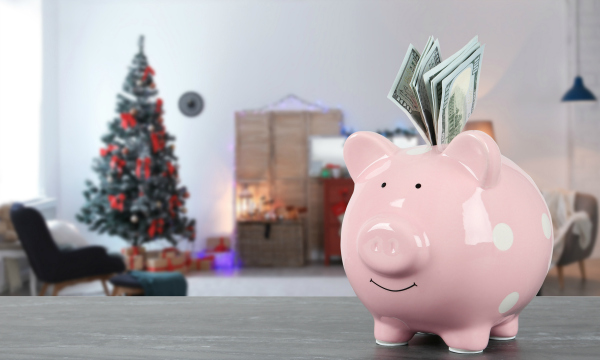 Piggy bank with money on table in living room decorated for Christmas.