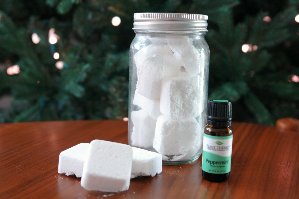 shower steamers in jar on table with bottle of essential oils