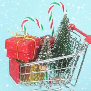 Shopping cart with christmas gifts an christmas tree on blue background