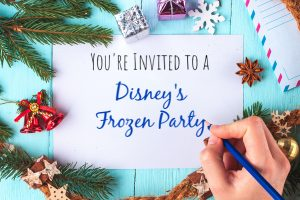desk with christmas items and piece of paper that says you're invited to a Disney's frozen party