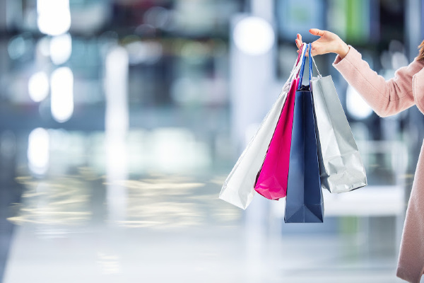 woman in coat holding shopping bags in mall