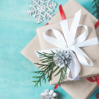 Several Christmas boxes of gifts festively decorated on a turquoise background