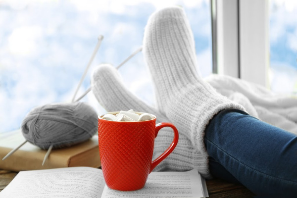 feet in warm socks with cup of hot cocoa and knitting
