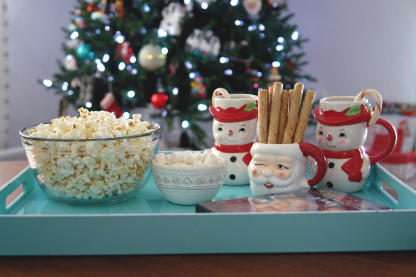 Aqua tray with popcorn and hot chocolate in front of Christmas tree