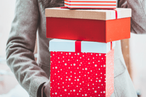 woman holding christmas gifts wrapped in red wrapping paper
