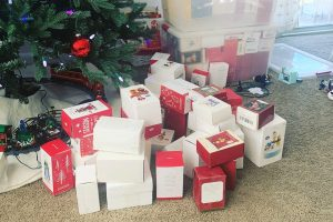 pile of Hallmark ornament boxes in front of tree