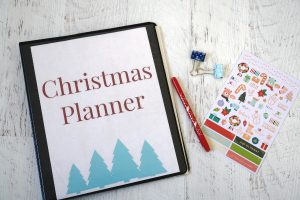 christmas planner with pens and stickers on white table