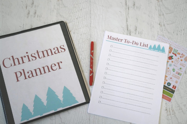 Christmas planner and stack of printable Christmas planner pages, pen and stickers on table