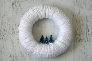 white christmas wreath with small christmas trees