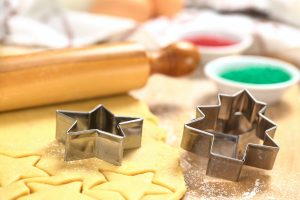 Cookie cutter on rolled out sugar cookie dough with rolling pin